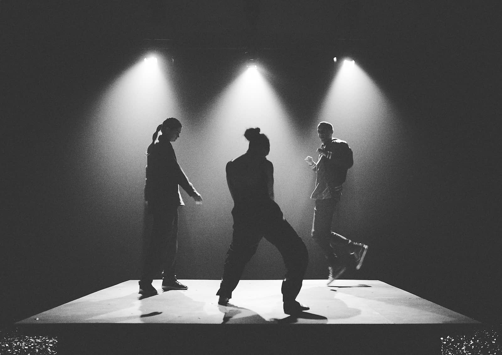 Three dancers are silhouetted in bright spot lights as part of Showcase Victoria