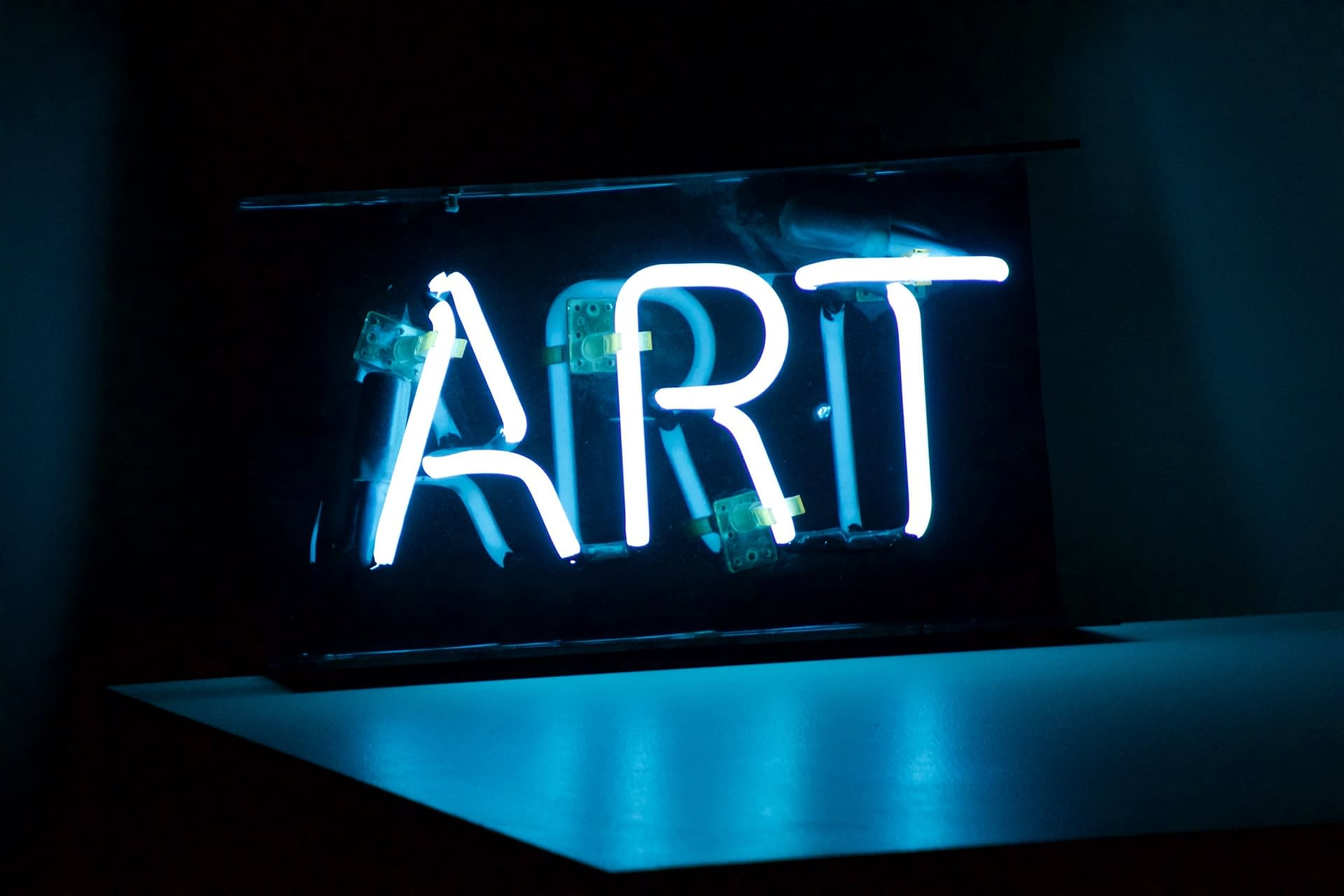 Neon sign spelling out the work ART in bright blue light